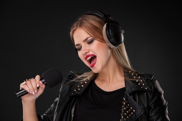 Portrait of a beautiful woman singing into microphone with headphones in studio on black Free Photo