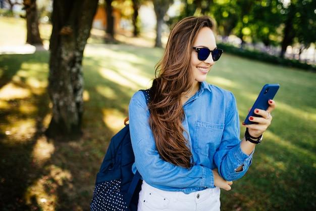 Ritratto di una bella donna in occhiali da sole digitando sullo smart phone in un parco con uno sfondo verde sfocato Foto Gratuite