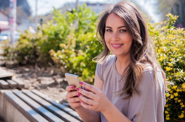 Portrait of a beautiful woman typing on the smart phone in a park with a green unfocused background. cheerful woman texting with her smartphone in a park Free Photo