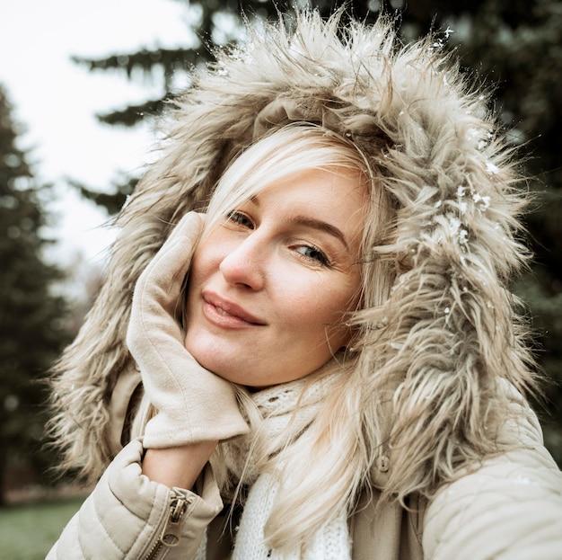 Ritratto di una bella donna che indossa giacca invernale con cappuccio Foto Gratuite