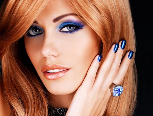 Ritratto di una bella donna con unghie blu, trucco blu e lunghi capelli rossi sul muro nero Foto Gratuite
