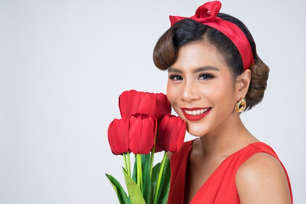 Portrait of beautiful woman with bouquet of red tulip flowers Free Photo