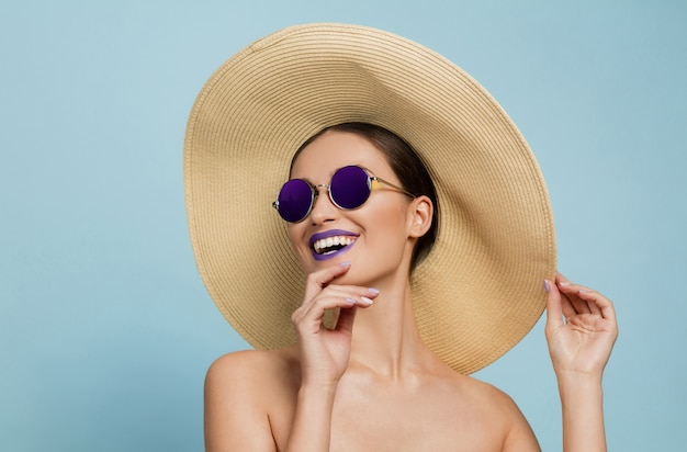 Portrait of beautiful woman with bright make-up, hat and sunglasses on blue studio background. stylish and fashionable make and hairstyle. colors of summer. beauty, fashion and ad concept. laughting. Free Photo