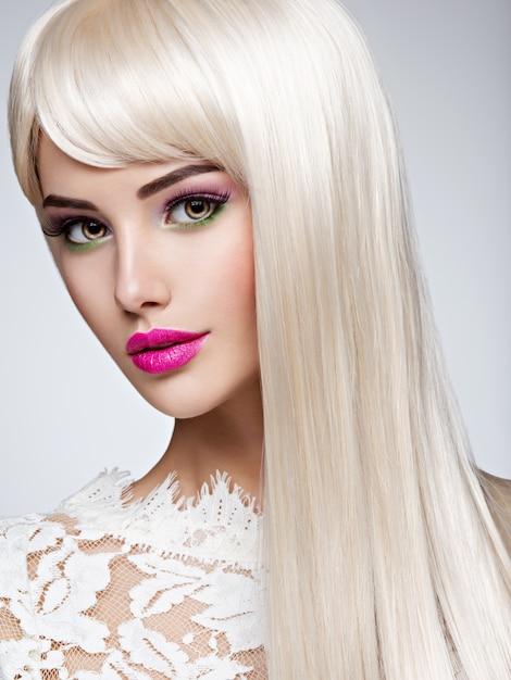 Ritratto di una bella donna con lunghi capelli lisci bianchi e trucco luminoso. volto di una modella con rossetto rosa. bella ragazza in posa. Foto Gratuite