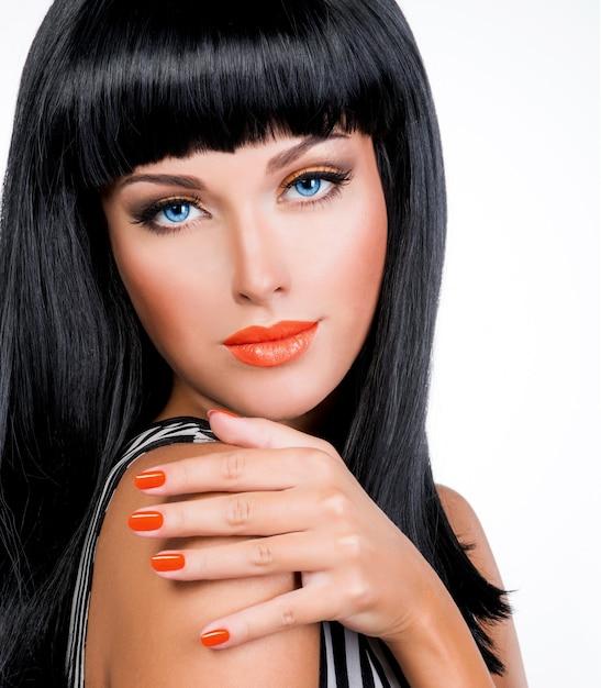 Ritratto di una bella donna con unghie rosse e trucco glamour e lunghi capelli neri Foto Gratuite