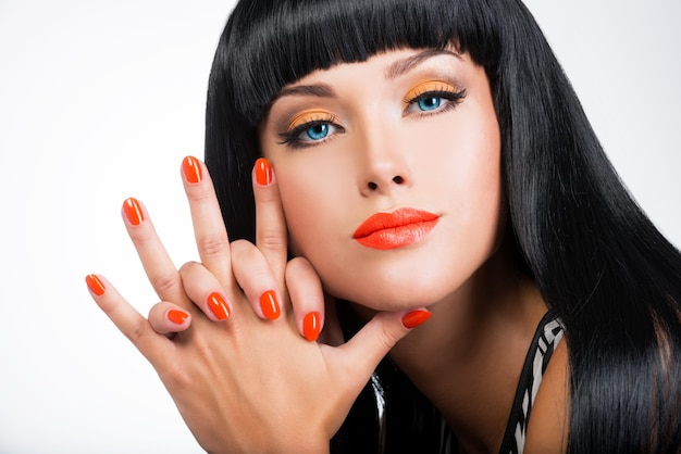 Portrait of a beautiful woman with red nails and glamour makeup and  long black hairs Free Photo