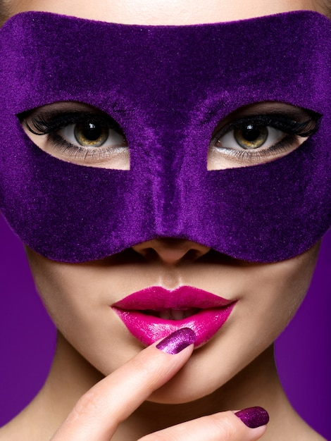 Portrait of a beautiful  woman with violet nails and theatre mask on face. Free Photo