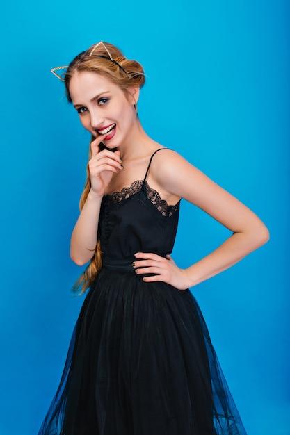 Ritratto di donna bella, giovane donna in posa alla festa, mordere il dito. indossa un abito nero fantasia, cerchietto con orecchie di gatto in diamanti, manicure dorata. Foto Gratuite