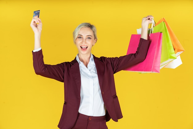 Portrait of beautiful women holding shopping bags with credit card and enjoying shopping on yellow Premium Photo