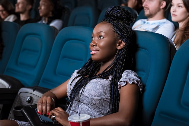 Portrait of a beautiful young african woman smiling looking at the screen attentively while enjoying watching a movie at the local cinema Premium Photo