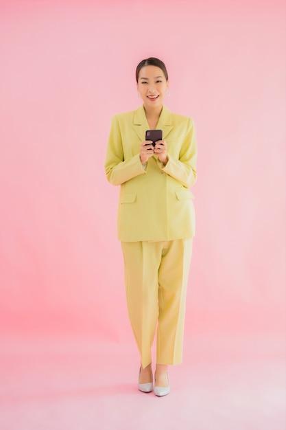 Мобильный телефон пользы бизнес-леди портрета красивой молодой азиатской умный с кофейной чашкой на цвете Бесплатные Фотографии