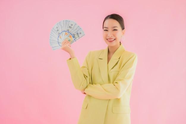 多くの現金または色のお金を持つ美しい若いアジアビジネス女性の肖像画 無料写真