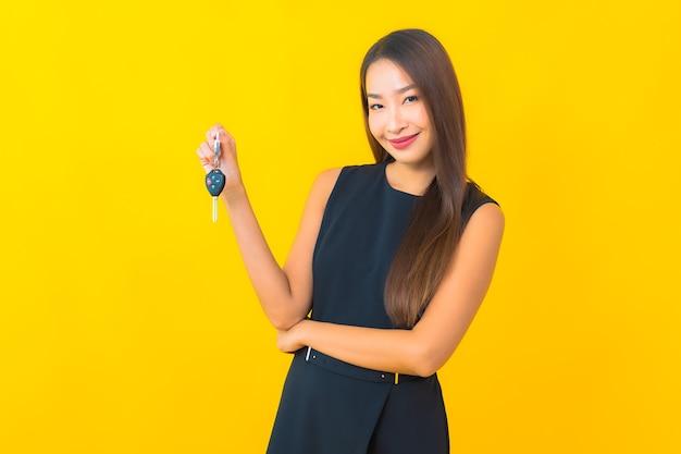 노란색 배경에 자동차 키와 세로 아름 다운 젊은 아시아 비즈니스 우먼 무료 사진