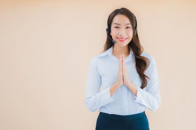 コールセンターのヘッドフォンで美しい若いアジアビジネス女性の肖像画 無料写真