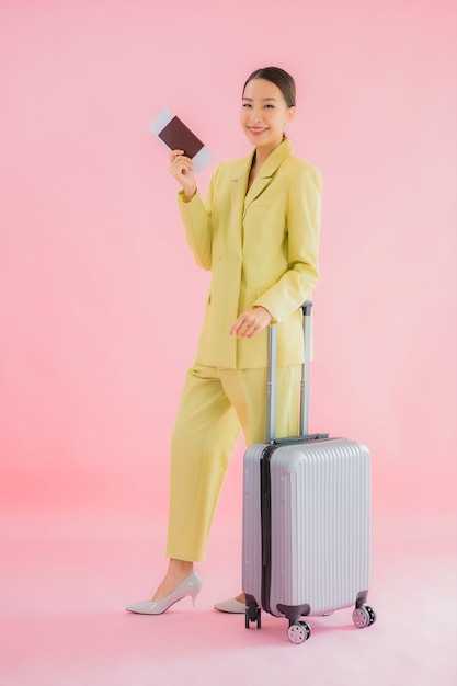 Портрет красивой молодой азиатской бизнес-леди с багажной сумкой и паспортом на цвете Бесплатные Фотографии
