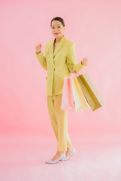 分離された色の買い物袋を持つ美しい若いアジアビジネス女性の肖像画 無料写真