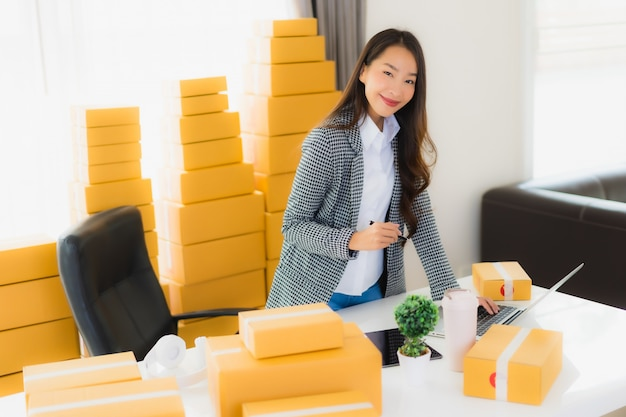 Portrait beautiful young asian business woman work from home with laptop mobile phone with cardboard box ready for shipping Free Photo