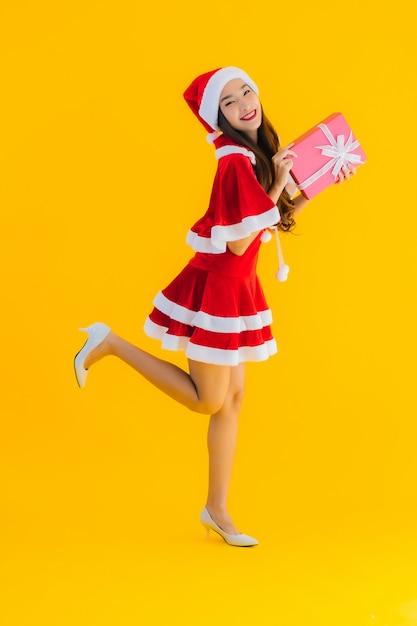 肖像画の美しい若いアジアのクリスマスの服と帽子笑顔赤いギフトボックスに満足 無料写真