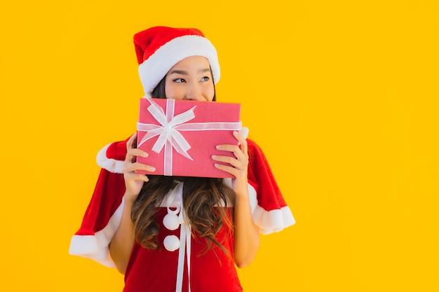 Одежды рождества портрета красивые молодые азиатские и улыбка шляпы счастливые с красной подарочной коробкой Бесплатные Фотографии