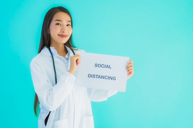 Portrait beautiful young asian doctor woman with sign paper with social distancing Free Photo