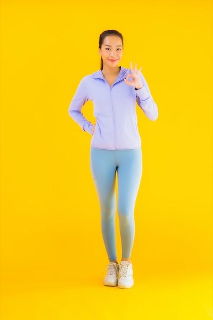 Bella giovane donna asiatica di sport del ritratto pronta per l'esercizio su giallo Foto Gratuite
