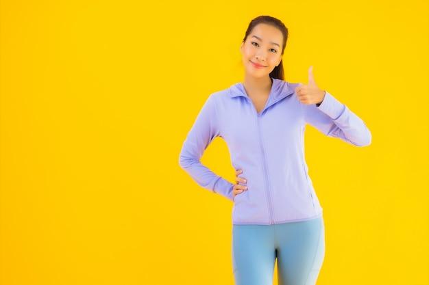 Женщина спорта портрета красивая молодая азиатская готовая для тренировки на желтом цвете Бесплатные Фотографии