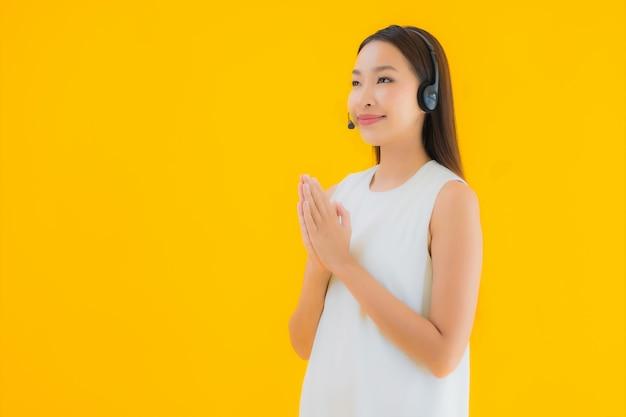Callcenter della bella giovane donna asiatica del ritratto per l'assistenza Foto Gratuite