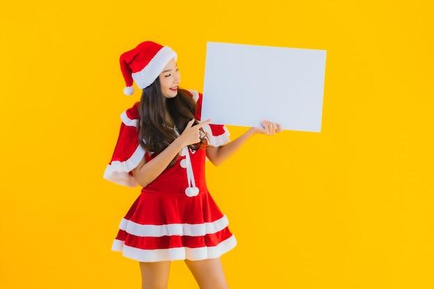 Одежды рождества женщины портрета красивые молодые азиатские и улыбка шляпы с пустой доской Бесплатные Фотографии