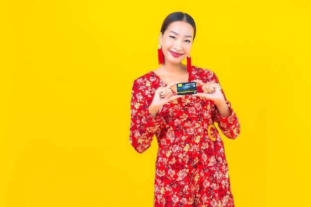 Кредитная карта женщины портрета красивая молодая азиатская для покупок на желтой изолированной стене Бесплатные Фотографии