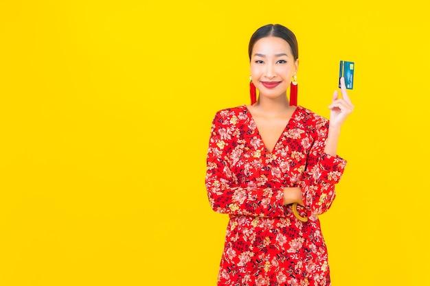 노란색 격리 된 벽에 쇼핑을위한 초상화 아름 다운 젊은 아시아 여자 신용 카드 무료 사진