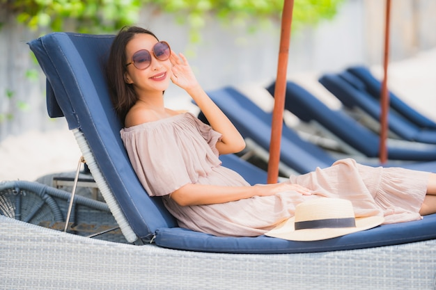 Portrait beautiful young asian woman on the deck chair with umbrella around beach sea ocean Free Photo