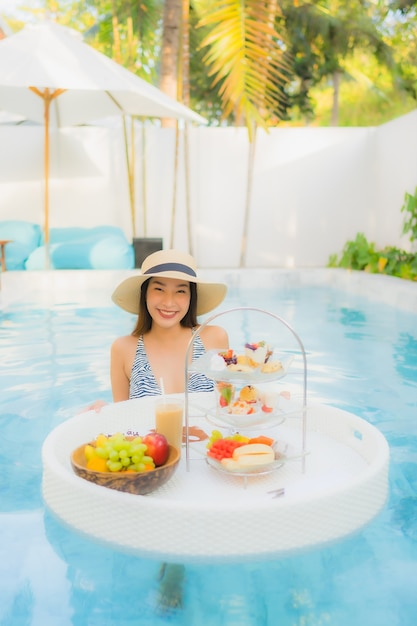 Portrait beautiful young asian woman enjoy with afternoon tea or breakfast floating on swimming pool Free Photo