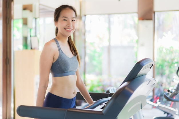 Portrait beautiful young asian woman exercise with fitness equipment in gym interior Free Photo