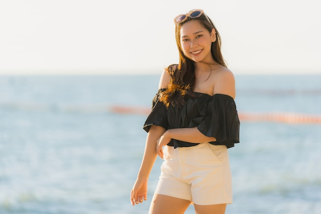 Portrait beautiful young asian woman happy and smile on the beach sea and ocean Free Photo