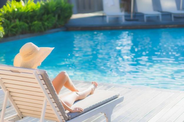 Il sorriso felice della bella giovane donna asiatica del ritratto si rilassa intorno alla piscina all'aperto nella località di soggiorno dell'hotel Foto Gratuite