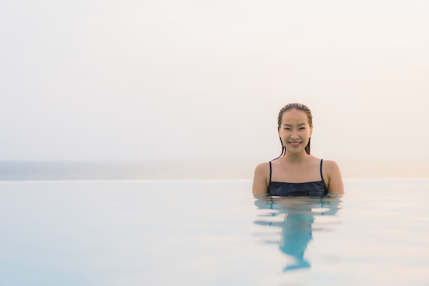 Portrait beautiful young asian woman happy smile relax around swimming pool in hotel resort Free Photo