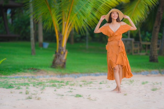 Portrait beautiful young asian woman happy smile relax on the beach sea ocean Free Photo