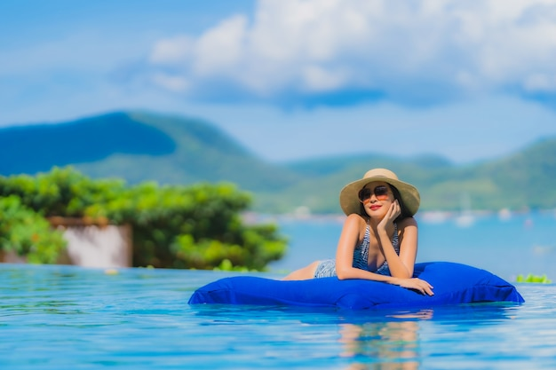 Portrait beautiful young asian woman happy smile relax in swimming pool at hotel resort neary sea ocean beach on blue sky Free Photo