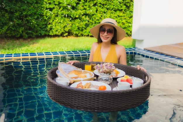 Portrait beautiful young asian woman happy smile relax with breakfast floating around swimming pool Free Photo