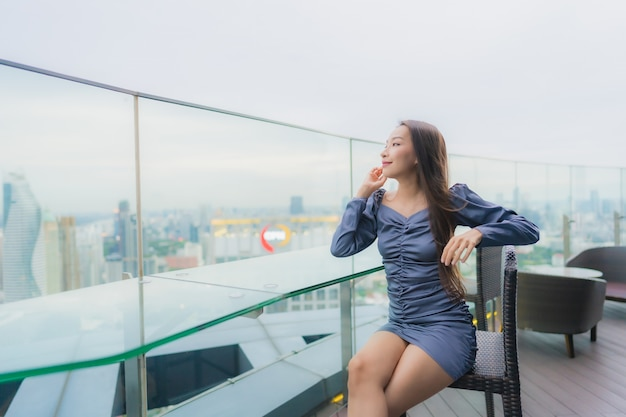 Portrait beautiful young asian woman happy smile on roof top restaurant around city view Free Photo