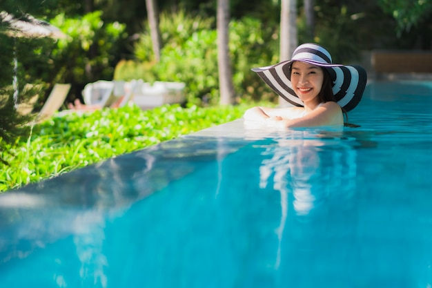 Portrait beautiful young asian woman happy smile in swimming pool around resort and hotel Free Photo