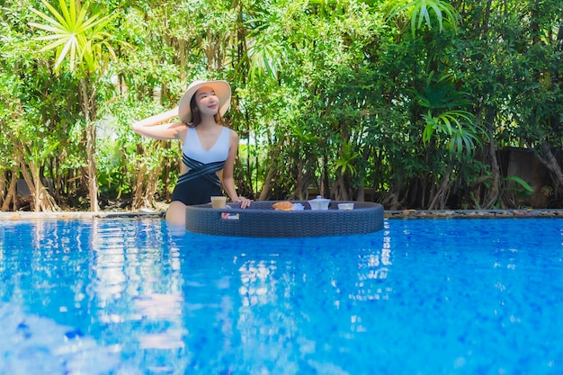 Portrait beautiful young asian woman happy smile with floating breakfast in tray on swimming pool Free Photo