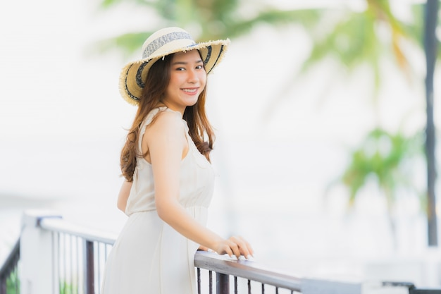 Portrait beautiful young asian woman happy and smile with travel in hotel resort neary sea and beach Free Photo