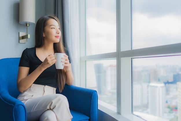 肖像画の美しい若いアジアの女性は、リビングルームのソファーの椅子にコーヒーカップを保持します。 無料写真