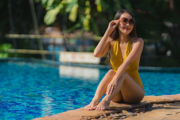 Portrait beautiful young asian woman leisure relax smile and happy around swimming pool in hotel resort Free Photo