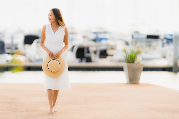 Portrait beautiful young asian woman leisure smile happy relax around yacht port Free Photo