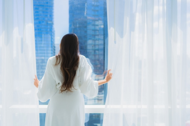 Взгляд женщины портрета красивый молодой азиатский вне окна для взгляда Бесплатные Фотографии