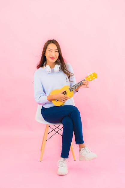 La bella giovane donna asiatica del ritratto gioca l'ukulele sulla parete isolata di colore rosa Foto Gratuite