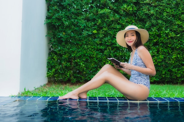 Portrait beautiful young asian woman read book around swimming pool Free Photo