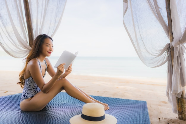 Portrait beautiful young asian woman reading book with happy smile relax in lounge bed chair on the beach sea ocean for leisure Free Photo